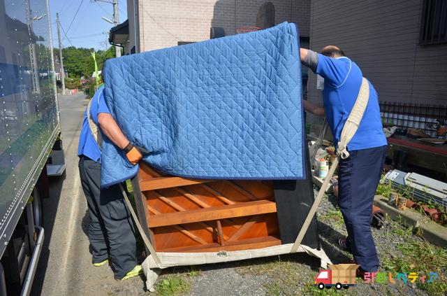 ピアノ運送専門業者がピアノを運んでいる様子