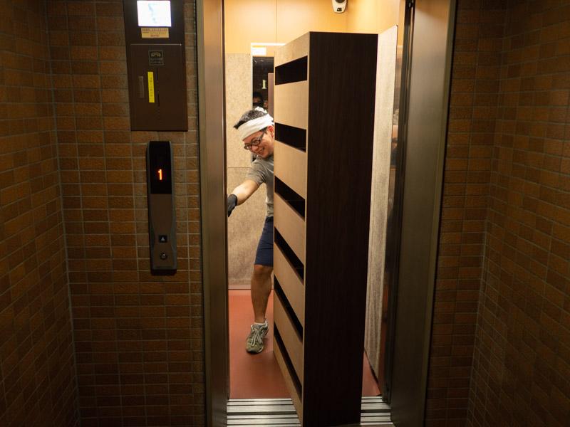 大きい本棚を自分一人でエレベーターに運び出す