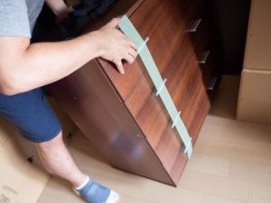洋ダンスは運搬時に棚が出てしまうため養生テープを貼る